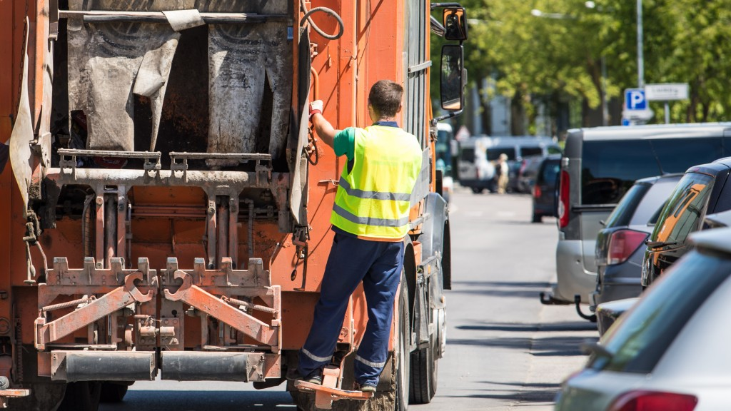 A worker rides on the back of a collection truck