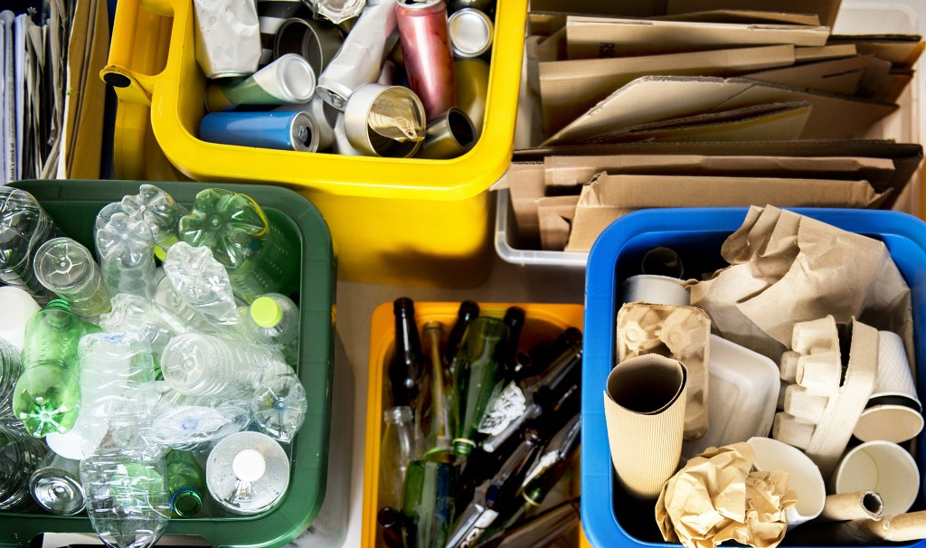Various types of recyclable materials sorted into different coloured bins
