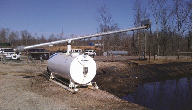 A tube-based oil skimming system in place next to a frac water pond, above. Tubebased skimmers gather oil and other materials from the water; those materials are then stripped from the tube within the system and recovered.