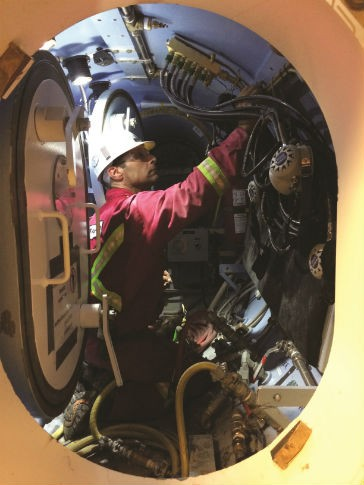 A member of the hyperbaric intervention support team, inside the airlock. The workers are often certified commercial divers.