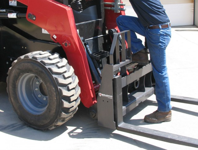 Walk‐Thru Pallet Forks allows the operator to step through the frame upon entry and exit for safe access to the loader.