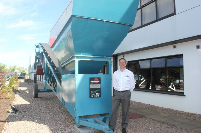 Colin Clements, Global Product Line Director beside a 1966 MK1 screening machine.   This was the sixth machine built and remains a permanent feature at the Dungannon Plant.
