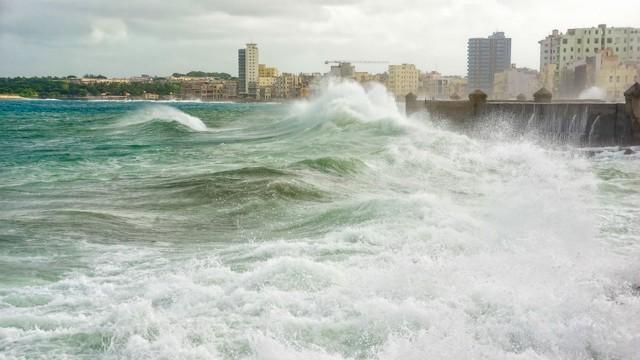 Storm surge attacks a seawall protecting coastal city.