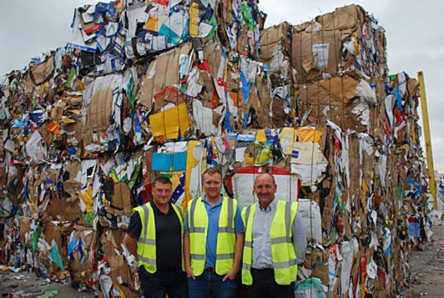Kadant's Jason Greatorex (left), Lee and Steve Evans, at the Parry & Evan recovered fiber facility in Deeside, Wales. The bales behind them will go to Asia, where inspections will verify their high quality.
