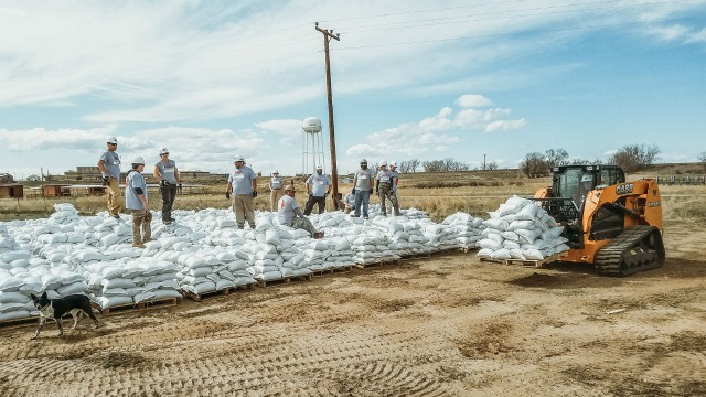 Team Rubicon crews work with a Case CTL to prepare for high waters in Fremont County, Wyoming.