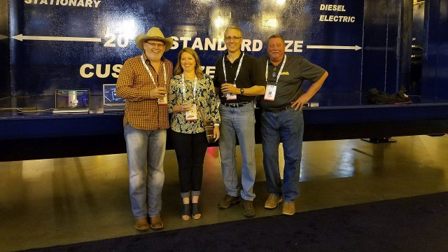 The owners of OverBuilt, at ISRI in April, in front of a 2018 Model 10 HS Car Crusher. From left to right: Gary Reichling, Kellee Pace and Don Roby, along with sales manager Steve Besch.