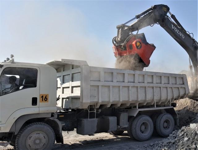 The Allu Transformer processing bucket attachment screening waste material into fine soil.
