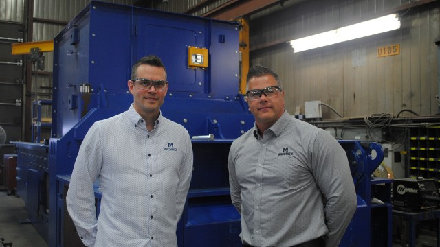 Left to right: Jonathan Fortier and Sébastien Delisle in front of a baler inside the Machinex manufacturing facility.